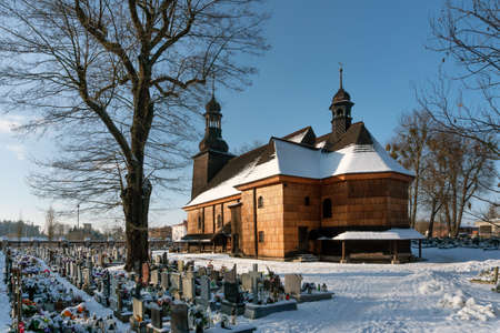 KOSZECIN, POLAND JANUARY 31,2021: Originating from 1724, the Holy Trinity Church was built of wood on the foundation of stone and brick. It is part of the Wooden Architecture Trail of the Silesian Voivodeship. Editorial