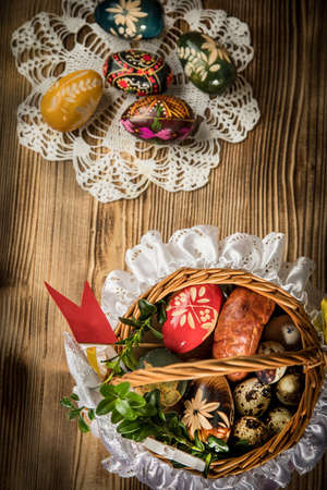 Traditional Easter basket with colored eggs on the wooden table.