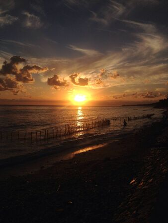 blown away: A seaweed farmer in nusa penida is trying to find seaweed which is blown away by the wave at sunrise
