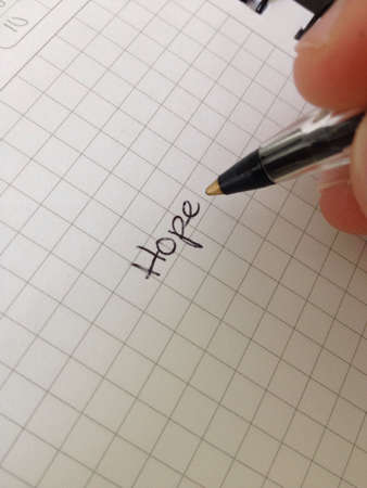 hope: Man writing words on a paper Stock Photo