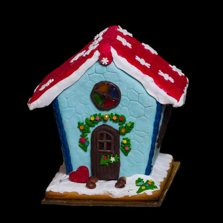 Small self-made gingerbread house isolated against black background close-up, selective focus, shallow DOF. Stock Photo