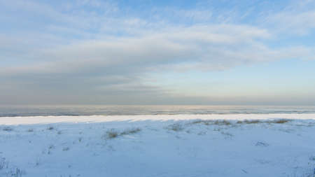 Winter shoreline of baltic sea with snow and ice under blue sky with clouds, selective focus. Standard-Bild - 111608953