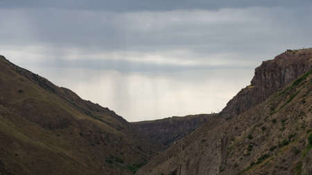 View of mountains landscape in Garni, Armenia, with clouds and distang rain arriving selective focus. Standard-Bild - 112395178