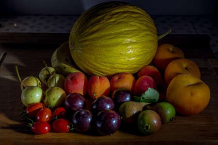 fresh seasonal fruits on wooden table with melon, pears, tomatoes, peaches, plums and apricots