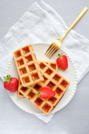 Top view of hot, fresh waffles and strawberries on a white plate with a fork on grey table top