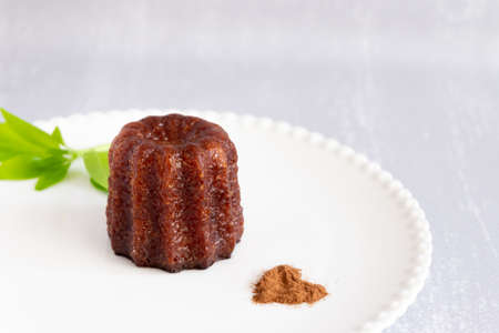 Canele, French confectionery, on a white and grey background