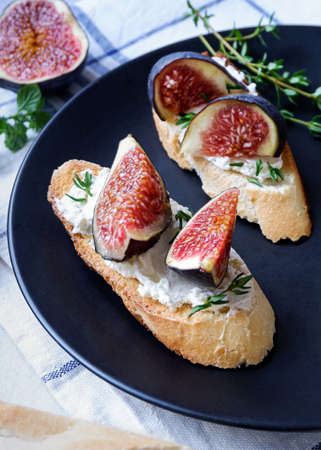 Two sandwiches with goat cheese, fig and thyme on fresh crispy bread served on a black plate on checked white and blue tablecloth