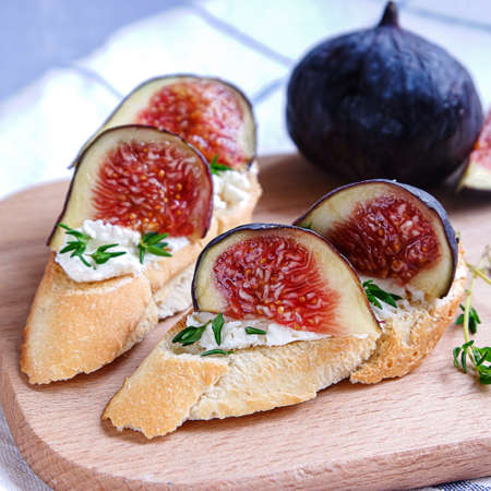 Close view of two sandwiches with goat cheese, fig and thyme on fresh crispy bread served on a wooden plate on light grey back 스톡 콘텐츠