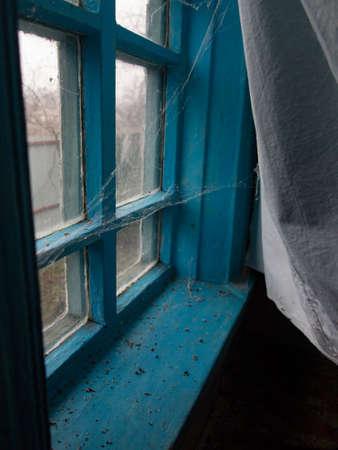 Ukrainian village house interior (old window frame with spider web)