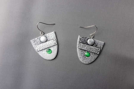 Hand made custom earrings polymer clay on grey fabric background lit from above 스톡 콘텐츠