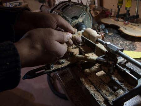 Zimmermann arbeitet an selbstgebauter Holzdrehmaschine mit Meißel