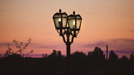 Vintage old lit lightpost at the dusk. Sunset sky on the background