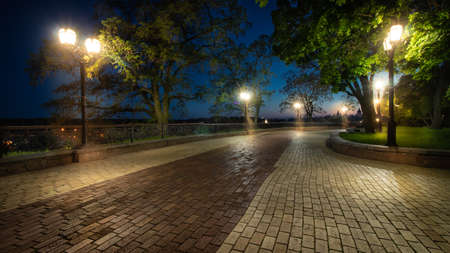 Empty city park landscape at the late evening or night with lit lightposts and wet brick road 스톡 콘텐츠