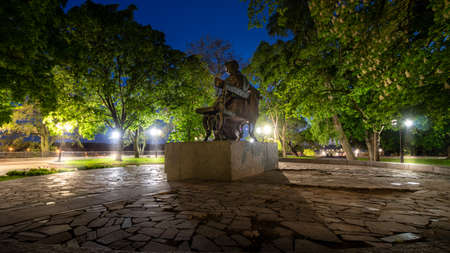 Empty city park landscape at the late evening or night with lit lightposts and Taras Shevchenko monument