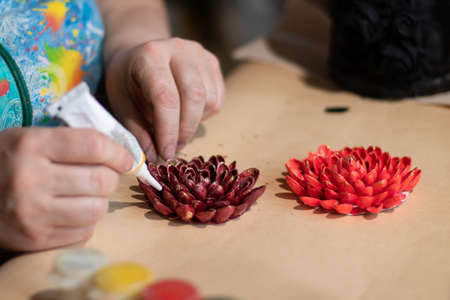Female artist is making a design of decorative flowers with painted nut shells