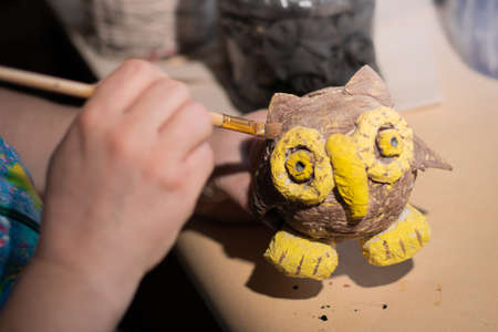 Female artist is using a painting brush on fairytale brown and yellow owl made of glued paper