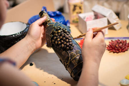 Female artist is using a painting brush on brown handmade bottle with leaves and grape made of coffee beans