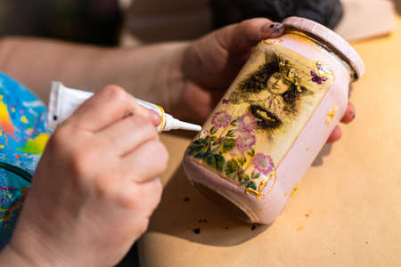 Female artist is using a glue on pink handmade glass can with a painting on it 스톡 콘텐츠