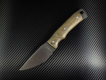 Custom hand forged knife with jeans micarta handles on carbon holstex background