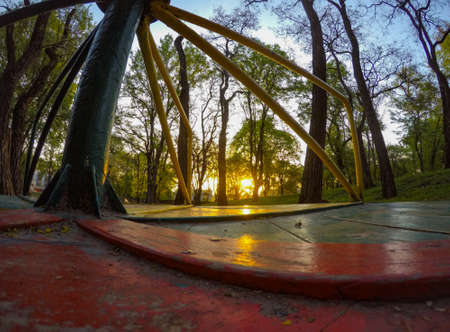Wide angle POV shot of merry-go-round at the playground. Point-of-view from the wooden floor. Shot at the spring morning. Barrel distortion 스톡 콘텐츠