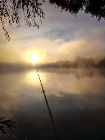 Fishing near lake at the early morning haze. Ukraine, Senkovka in Chernihiv region. Cloudy dawn scene