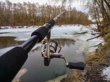 Fishing with spinning near lake covered wit melting thin ice. Ukraine, Chernihiv region. POV shot