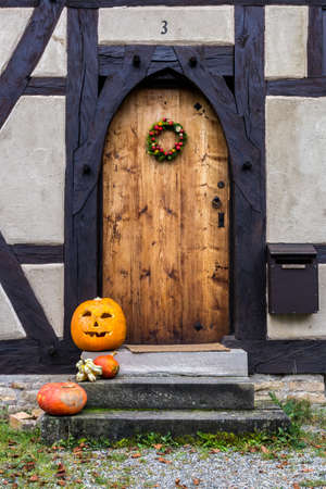 ancient medieval wooden door decorated for Halloween with two pumpkins in front