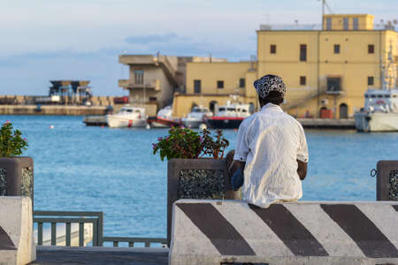 young african immigrant in the port of Agrigento Imagens