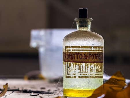 potassium: Abandoned bottle of yellow poison. Potassium chromate Stock Photo