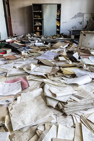 Abandoned office with many papers on the floor Imagens