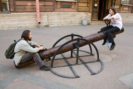 Young smiling couple sit on teeter-totter on street in summer Banque d'images