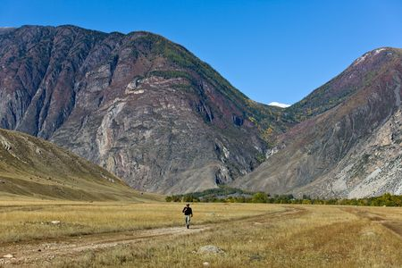 The lonely traveller on rural road to mountains Stock Photo - 6929977