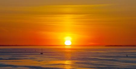 Heldere rode zonsondergang over de zee met wolken Stockfoto
