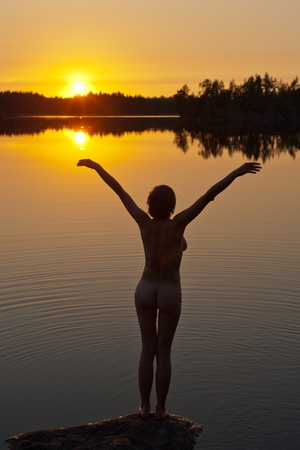 the woman on the bank of the lake at sunset Stock Photo - 13533585