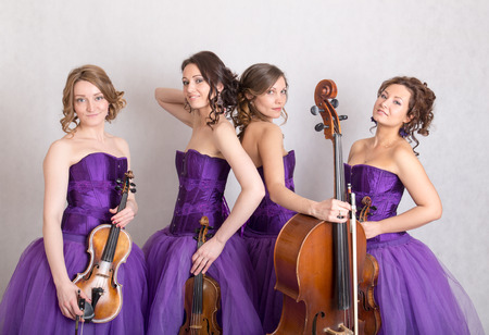 musical quartet in evening dresses with strings Stock Photo
