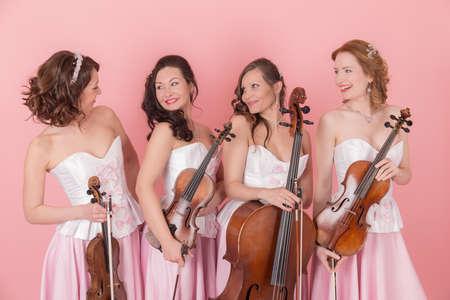 studio portrait of a string quartet on a pink background