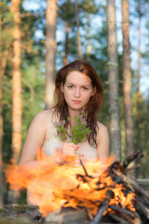 portrait of a beautiful naked girl by the fire Stock Photo