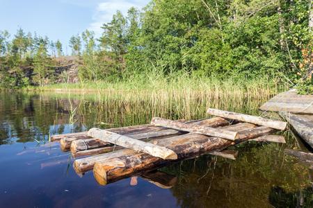 wooden raft near the shore of a forest lake Archivio Fotografico