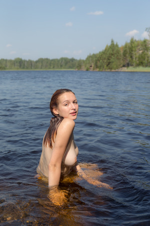 beautiful naked girl in the water of a forest lake