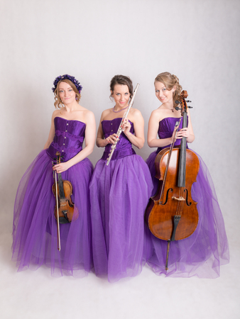 studio portrait of a musical trio in evening gowns