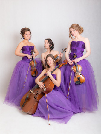 musical quartet in evening dresses with strings instruments Stock Photo