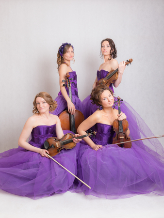 studio portrait of a musical quartet with instruments Stock Photo
