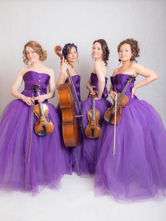 studio portrait of a musical quartet with instruments Stock Photo