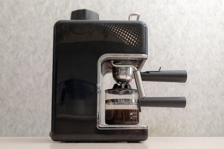 black coffee maker with coffee on the table