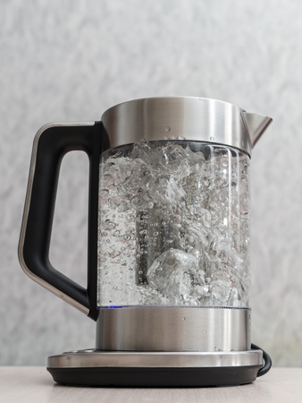 glass teapot with boiling water close up