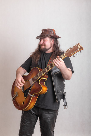 studio portrait of a musician playing a guitar