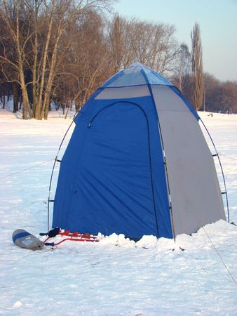 Tent on ice of a city pond with fishermen