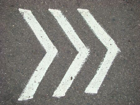 indicative: white pointers on an asphalt, indicative direction of motion