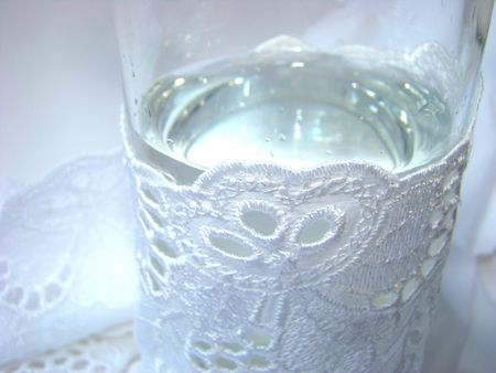 transparent glass with water is turned in white fabric with a lace