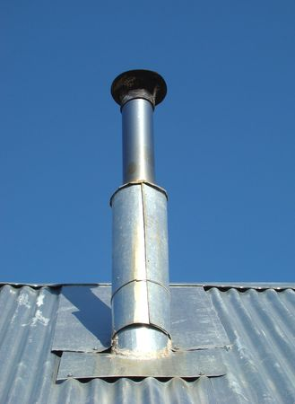 stove pipe: metallic flue on the roof of house Stock Photo